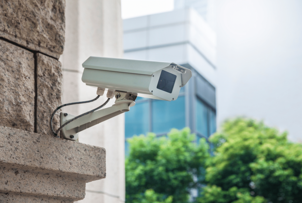 A security camera on a granite building wall