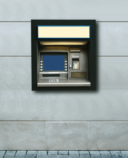 An ATM on a gray, stone wall with a cobblestone road below